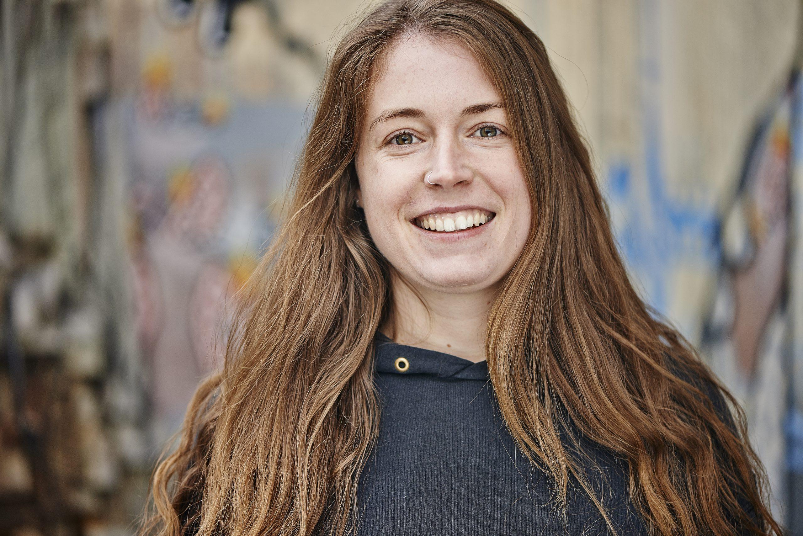 Portraitfoto einer jungen Frau mit braunen langen Haaren und einem offenen, freundlichem Lachen.