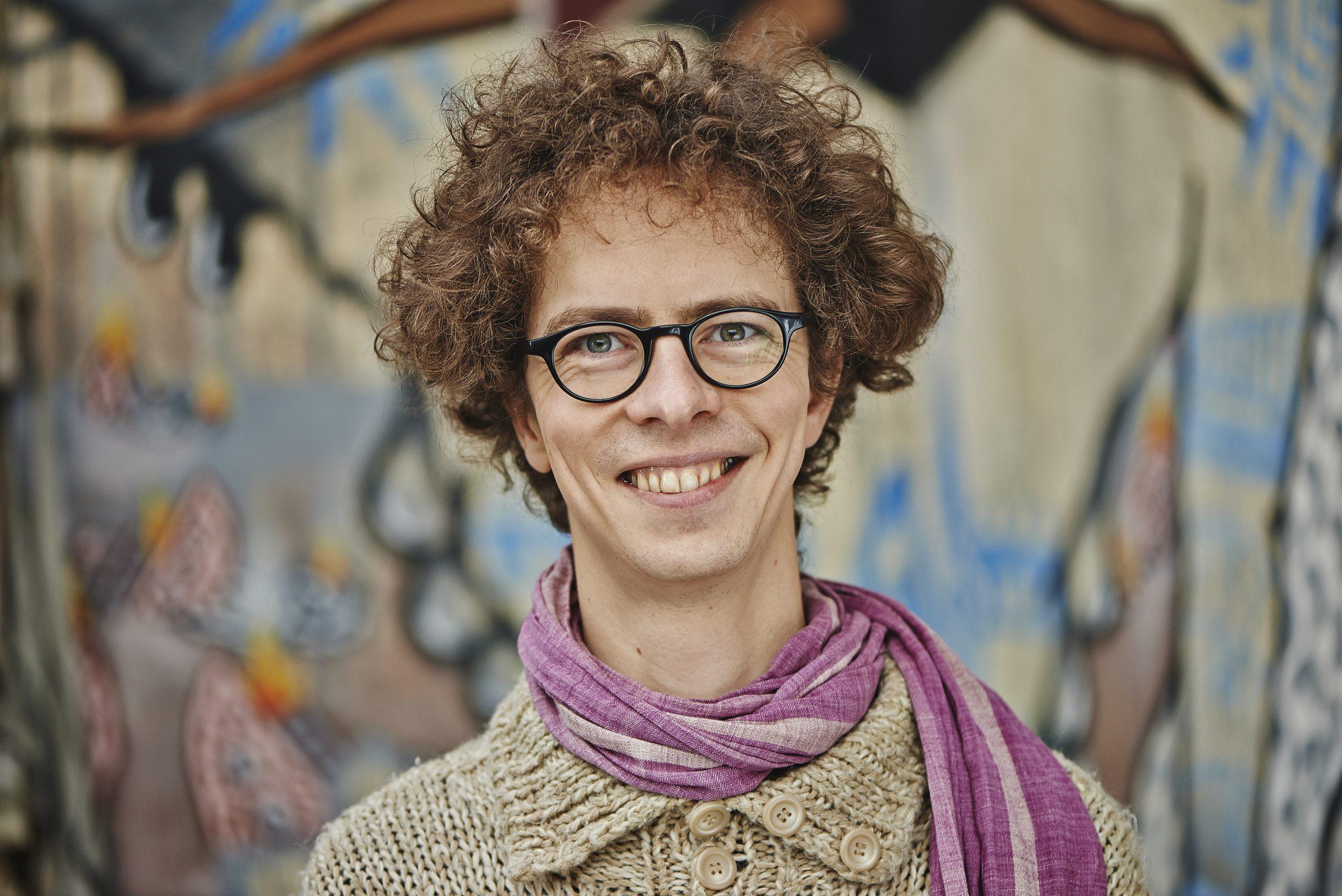 Portraitfoto eines jungen Mannes mit braunen lockigen Haaren. Er schaut lachend in die Kamera.