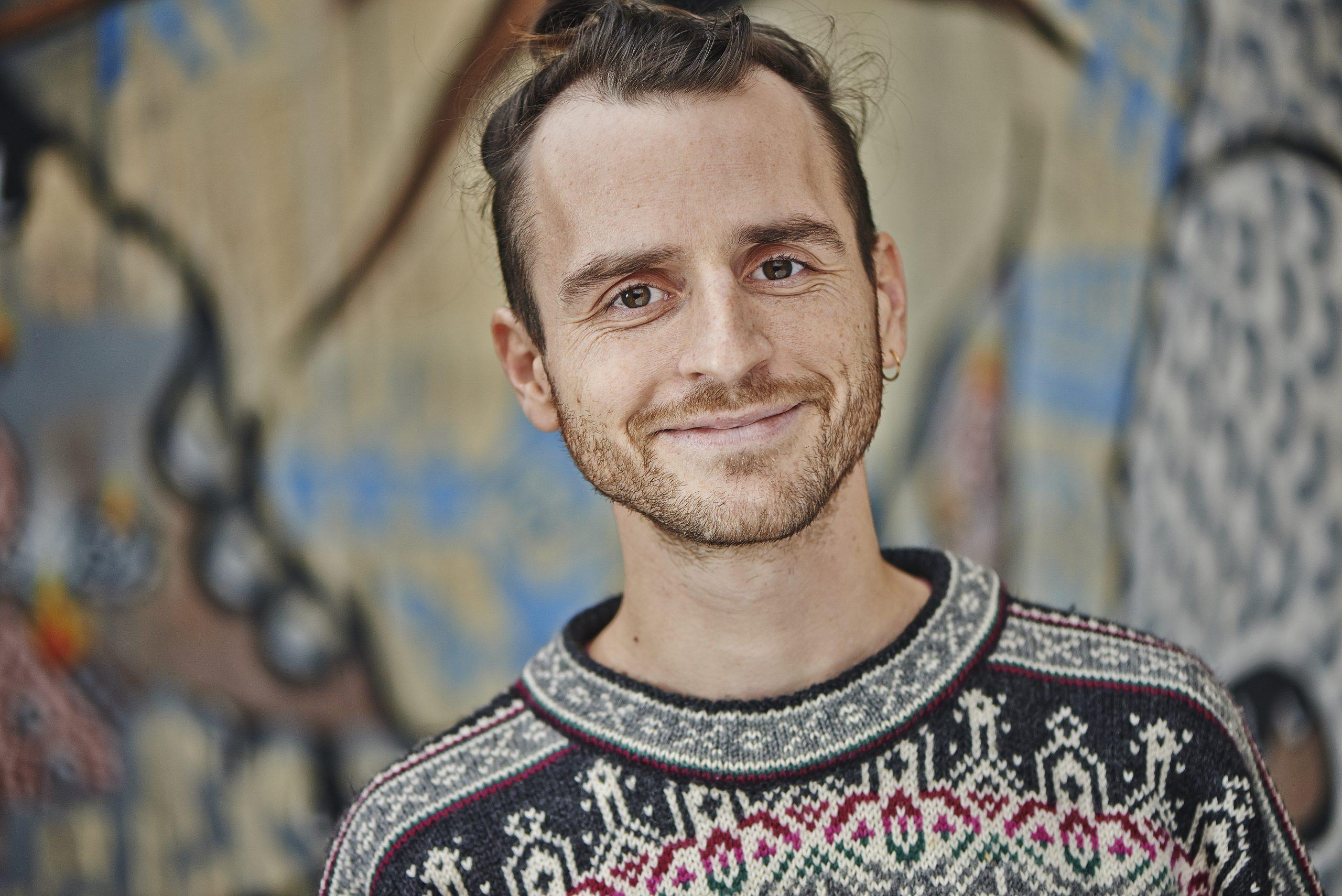 Portraitfoto eines jungen Mannes mit braunen Haaren. Er lächelt in die Kamera.