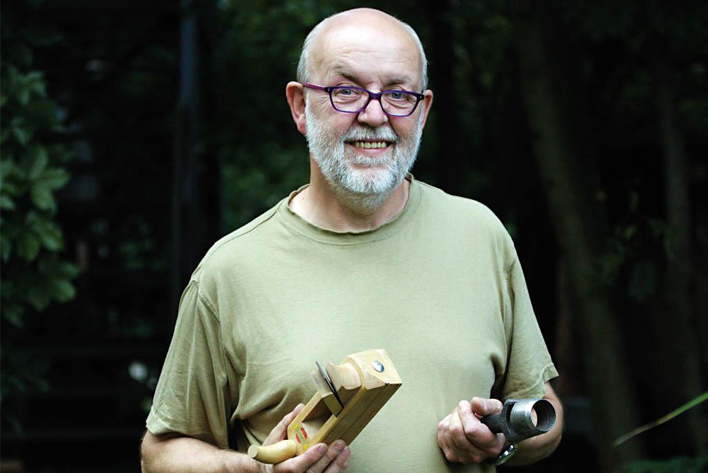 Portraitfoto eines älteren Mannes. Er hat graue Haare, Bart und lacht. In den Händen hält er einen Hobel.