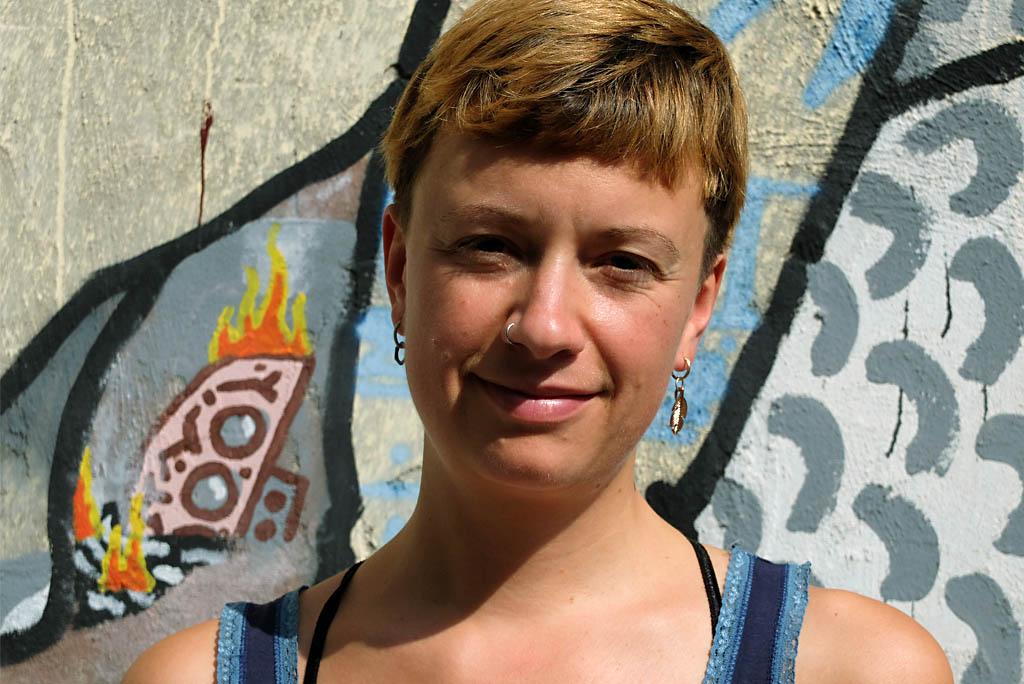 Portraitfoto einer jungen Frau mit kurzen goldbraunen Haare. Sie lächelt in die Kamera.