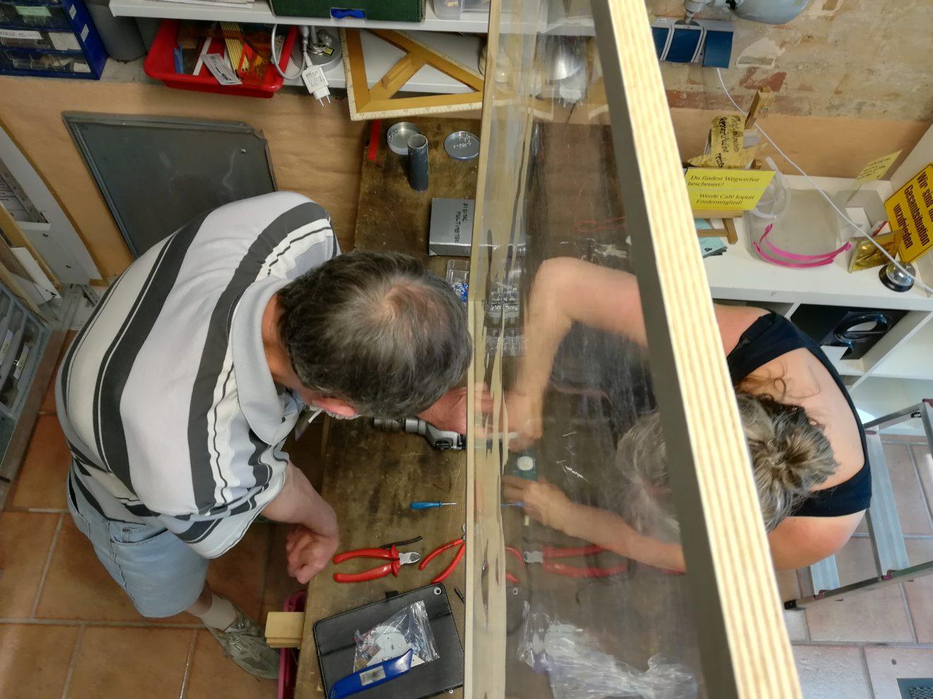 Bild: Reparieren während Corona mit Mundschutz und Plexiglastrennwand
